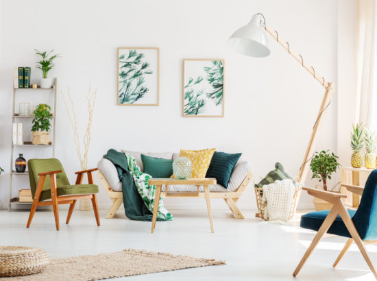 Designer lamp next to beige settee in living room with vintage chairs and pouf on carpet