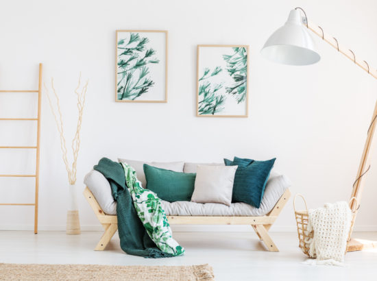 Leaves painting above sofa with green pillows and blanket in classic living room with designer lamp