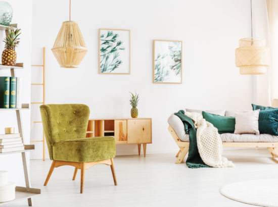 Two rattan lamps in bright living room with moss green chair and pineapple on shelf