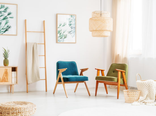 Two vintage chairs in bright room with ladder, pouf and paintings with floral motif on white wall