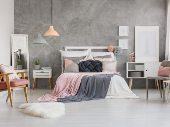 Pastel grey bedsheets on king-size bed against grey textured wall in adorable bedroom with powder pink