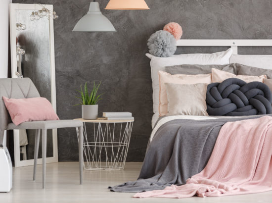 Pink pillow on grey modern chair in woman bedroom with pastel colored bedsheets on bed