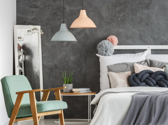 Vintage mint chair and mirror in pastel color bedroom with black knot pillow on bed against concrete wall